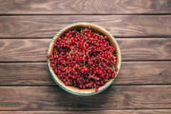 Fresh ripe red currant on a plate. Fresh ripe red currant in a bowl on a wooden background, top view stock photos