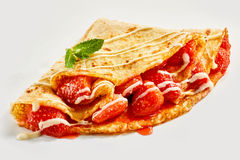 Fresh ripe red juicy strawberries in a crepe. Fresh ripe red juicy strawberries in a golden fried crepe or French pancake drizzled with cream and garnished with stock image