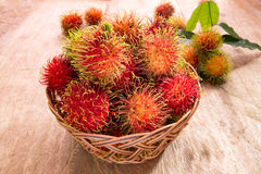 Fresh ripe red rambutans fruit in basket on wood floor. Rambutan is tropical of Southeast Asia fruit Royalty Free Stock Photo