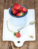 Fresh ripe red strawberries in blue enamel mug on white ceramic board over rustic wooden background Royalty Free Stock Photos