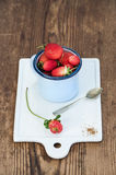 Fresh ripe red strawberries in blue enamel mug on white ceramic board over rustic wooden background Stock Images