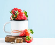 Fresh ripe red strawberries in country style enamel mug on rustic wooden board, pastel light blue background Stock Photos