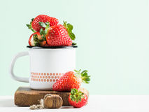 Fresh ripe red strawberries in country style enamel mug on rustic wooden board, pastel light mint background Royalty Free Stock Photos