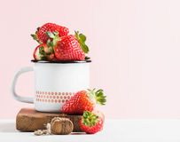 Fresh ripe red strawberries in country style enamel mug on rustic wooden board, pastel light pink background Stock Photography