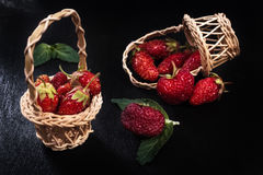 Fresh ripe red strawberry in a wooden basket and sprinkled berry at black  background Stock Photography