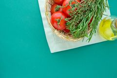 Fresh Ripe Red Tomatoes Rosemary Thyme in Wicker Basket Olive Oil in Bottle on White Napkin Green Background Italian Cuisine. Fresh Ripe Red Tomatoes Rosemary Stock Photos