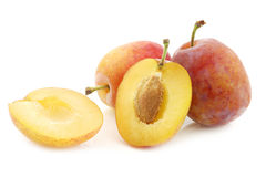Fresh ripe red and yellow plums and a cut one Royalty Free Stock Images