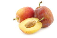 Fresh ripe red and yellow plums and a cut one Royalty Free Stock Photo