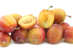 Fresh ripe red and yellow plums and a cut one Stock Images
