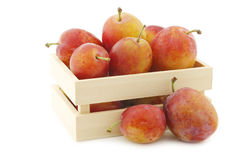 Fresh ripe red and yellow plums in a wooden box Royalty Free Stock Photos
