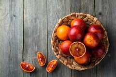 Fresh ripe Sicilian oranges and sliced pieces on a wooden old background. Selective focus. Top view