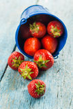 Fresh ripe strawberries in a blue bucket on a wooden background.  Royalty Free Stock Photography