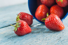Fresh ripe strawberries in a blue bucket on a wooden background.  Stock Photography