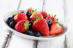Fresh ripe strawberries and blueberries. In a bowl on white backg royalty free stock photography