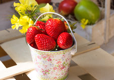 Fresh ripe strawberries in bucket on wood box in garden outdoors, fruits in basket in background Royalty Free Stock Photos