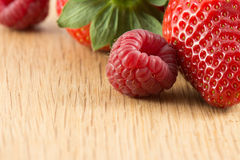 Fresh ripe strawberries and raspberries on wooden board Stock Photography