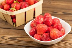 Fresh ripe strawberries in white bowl and wicker basket. On rustic wooden planks royalty free stock photo