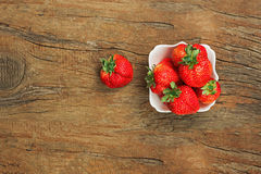 Fresh ripe strawberries in white bowl on wooden background. Royalty Free Stock Image