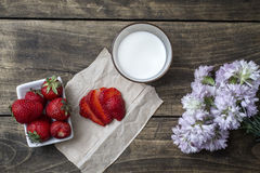 Fresh ripe strawberry in bowl and milk over wooden table backgro Royalty Free Stock Images