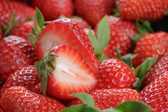 Fresh ripe strawberry with half in front Stock Photography