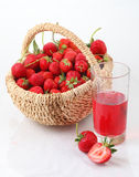 Fresh ripe strawberry in a wattled basket and a glass of strawbe. Still-life with a strawberry in a wattled basket and a glass of strawberry juice royalty free stock image