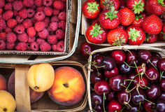 Fresh ripe summer berries and fruits in baskets royalty free stock photos