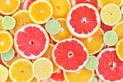 Fresh ripe sweet citrus fruits colorful background: orange, grapefruit, lime, lemon royalty free stock photography