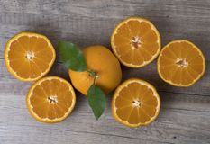 Fresh ripe tangerines with leaves on a wooden background royalty free stock images