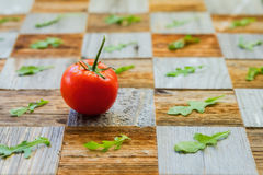 Fresh ripe tomato with water drops, basil leaves, surface mosaik board with pieces, different breeds as chess board. Fresh organic ripe tomatoes with water drops Royalty Free Stock Image