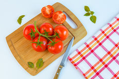 Fresh and ripe tomatoes, basil  and knife on cutting board Stock Photo