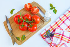 Fresh and ripe tomatoes, basil, salt and knife on cutting board Royalty Free Stock Image