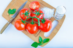 Fresh and ripe tomatoes, basil, salt and knife on cutting board Stock Photos