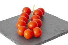 Freshly harvested cherry tomatoes on a stone plate. Fresh and ripe tomatoes on a black slate plate Royalty Free Stock Images