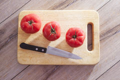 Fresh, ripe tomatoes on chopping board Royalty Free Stock Images