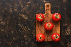 Fresh ripe tomatoes on a cutting board, dark background, top view. A copy of the space, flat lay. royalty free stock photo