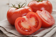 Fresh ripe tomatoes with halfs on wood table Stock Photography