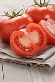 Fresh ripe tomatoes with halfs on wood table Stock Photo