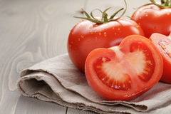 Fresh ripe tomatoes with halfs on wood table Royalty Free Stock Photo