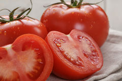 Fresh ripe tomatoes with halfs on wood table Stock Image