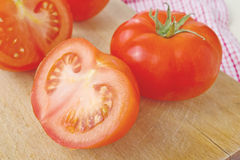 Fresh ripe tomatoes with halfs on wood table Stock Photos