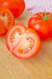 Fresh ripe tomatoes with halfs on wood table Royalty Free Stock Images