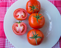 Fresh ripe tomatoes on white dish - top view.  royalty free stock images