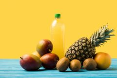 Fresh ripe tropical fruits and natural fruity drink in plastic bottle on turquoise wooden table royalty free stock images