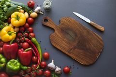 Fresh ripe vegetables with cutting board and knife on grey. Top view of fresh ripe vegetables with cutting board and knife on grey Stock Images