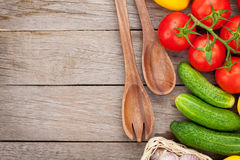 Fresh ripe vegetables and utensils on wooden table Royalty Free Stock Images