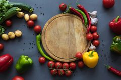 Fresh ripe vegetables with wooden cutting board on grey. Top view of fresh ripe vegetables with wooden cutting board on grey Stock Images