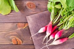 Fresh ripe washed radish on a cutting board on a wooden table. Top view Royalty Free Stock Photos