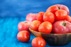 Fresh ripe wet red tomatoes in bowl. Fresh ripe wet red tomatoes in wooden bowl Royalty Free Stock Photography