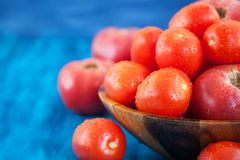 Fresh ripe wet red tomatoes in bowl. Fresh ripe wet red tomatoes in wooden bowl Royalty Free Stock Images