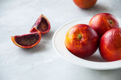 Fresh ripe whole and slices of blood oranges in a plate on a whi Royalty Free Stock Photos